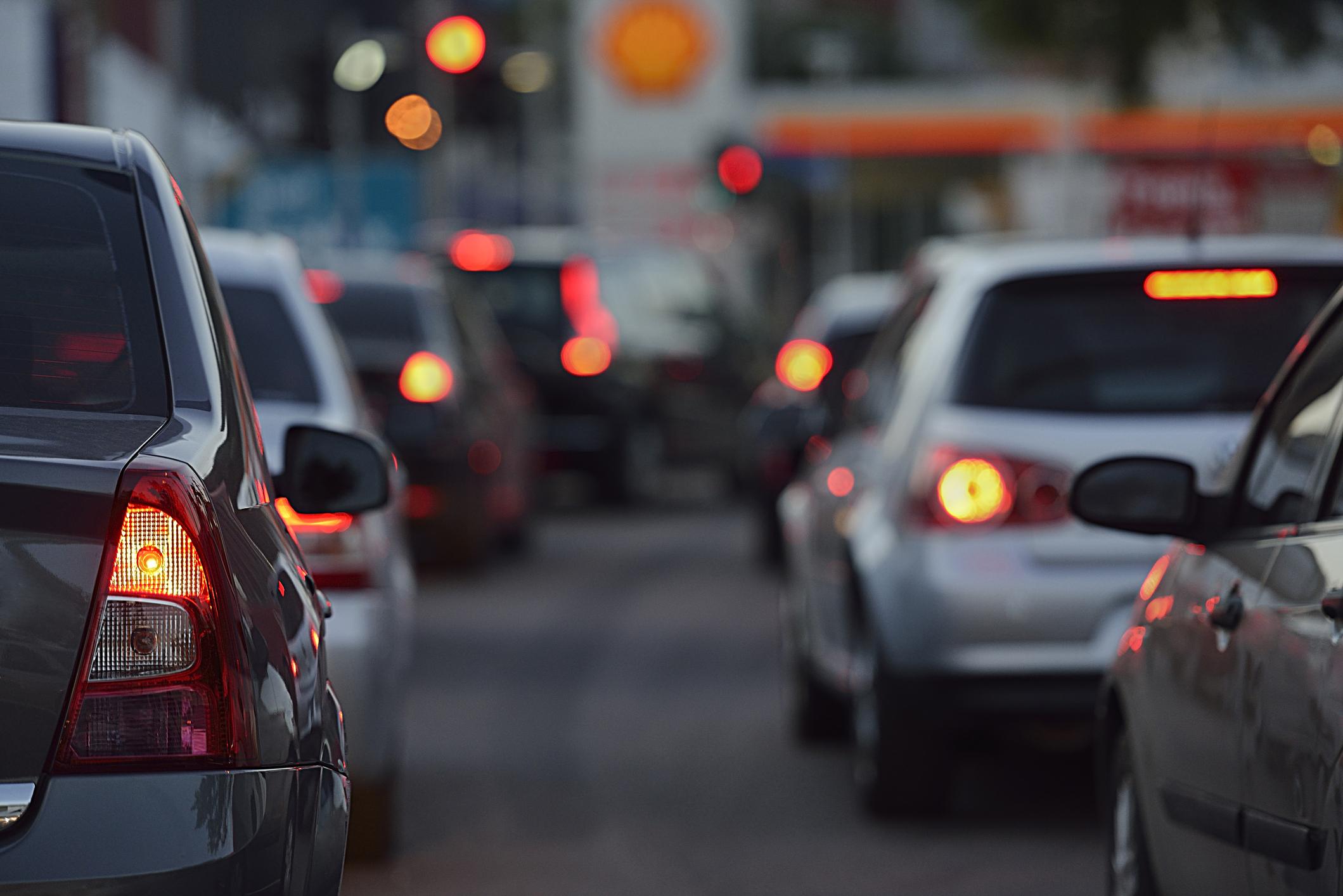 Autos stehen auf Straße im Stau bei Dämmerung