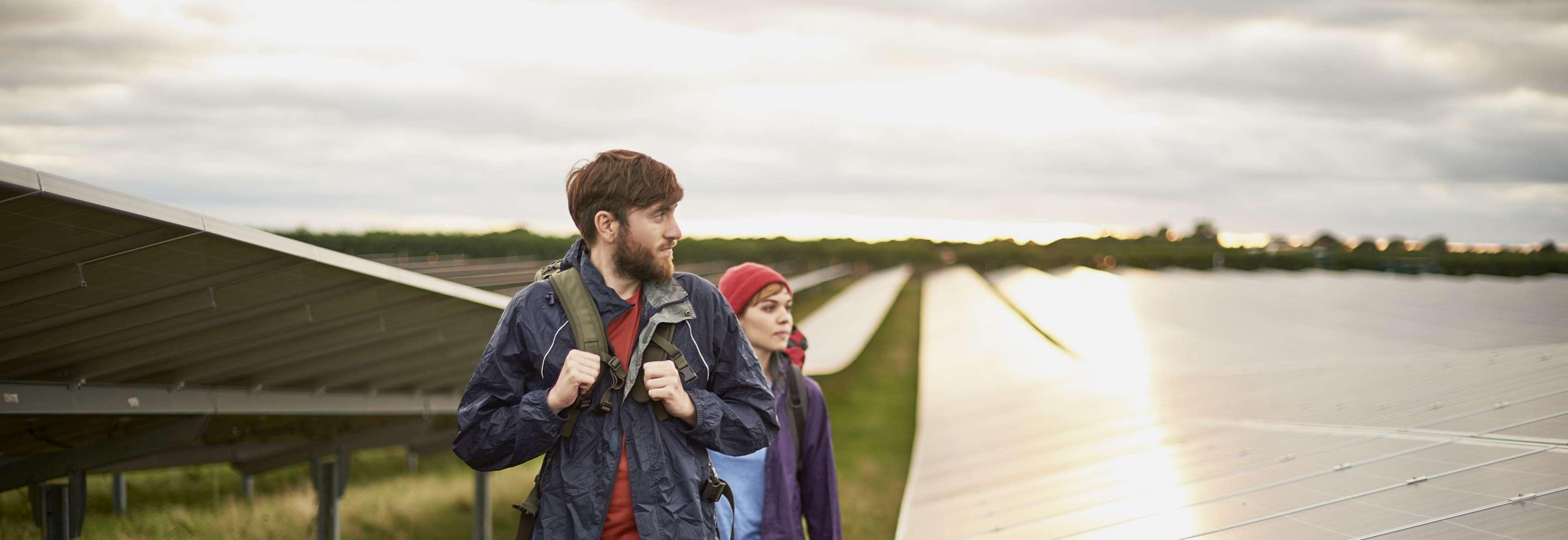 Ein junger Mann und eine junge Frau gehen auf einer Wiese mit Solarpanels entlang