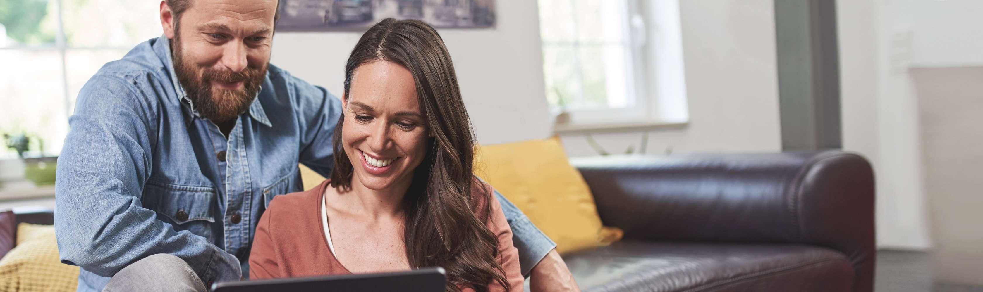 Ein junges Paar sitzt gemeinsam auf dem Sofa und blickt lächelnd auf ein Tablet.