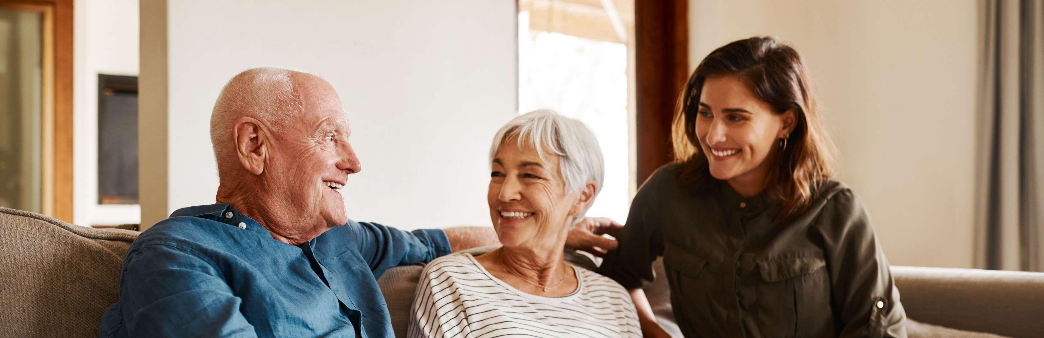 Risikolebensversicherun für Senioren und Rentner - Älteres Paar und junge Frau sitzen lachend auf einem Sofa