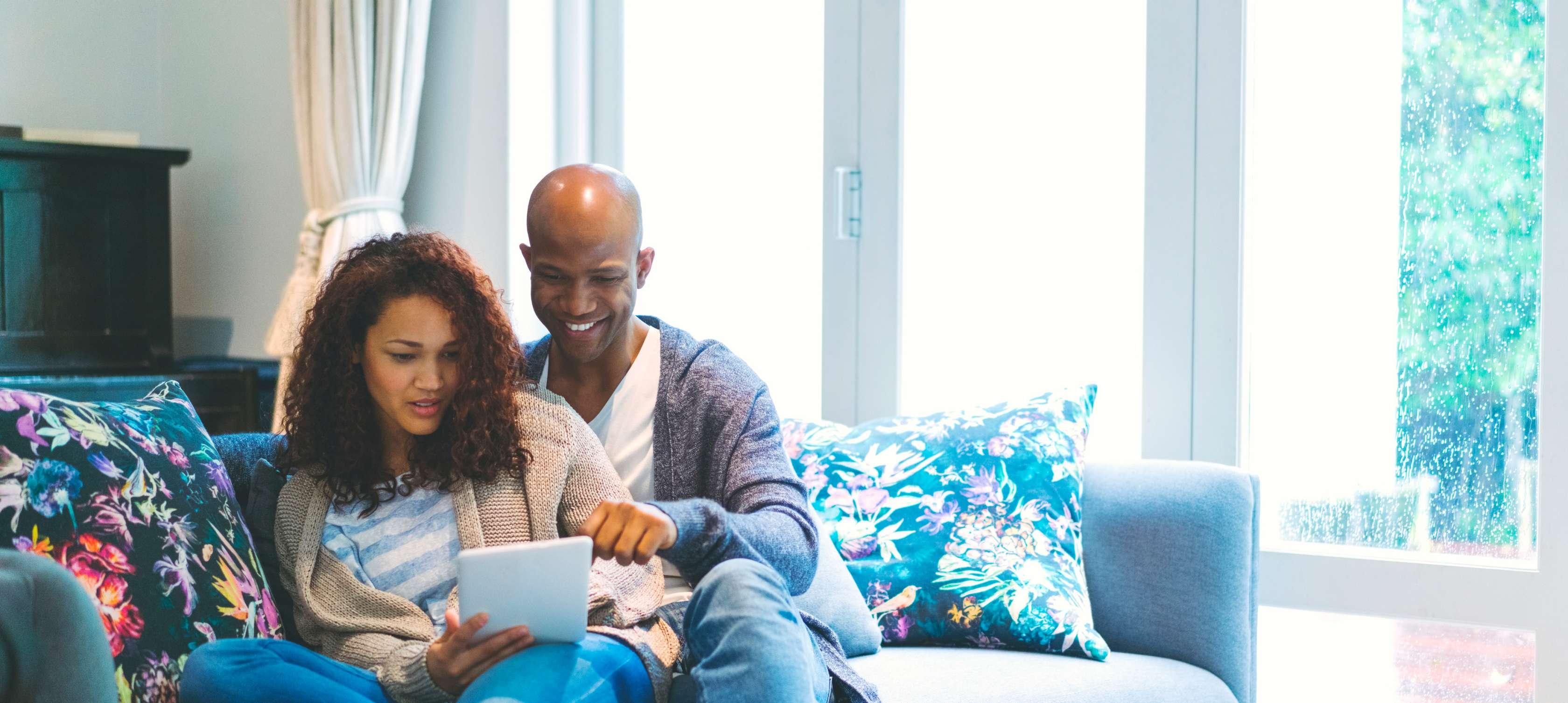 Junges Paar sitzt auf dem Sofa und recherchiert mit einem Tablet