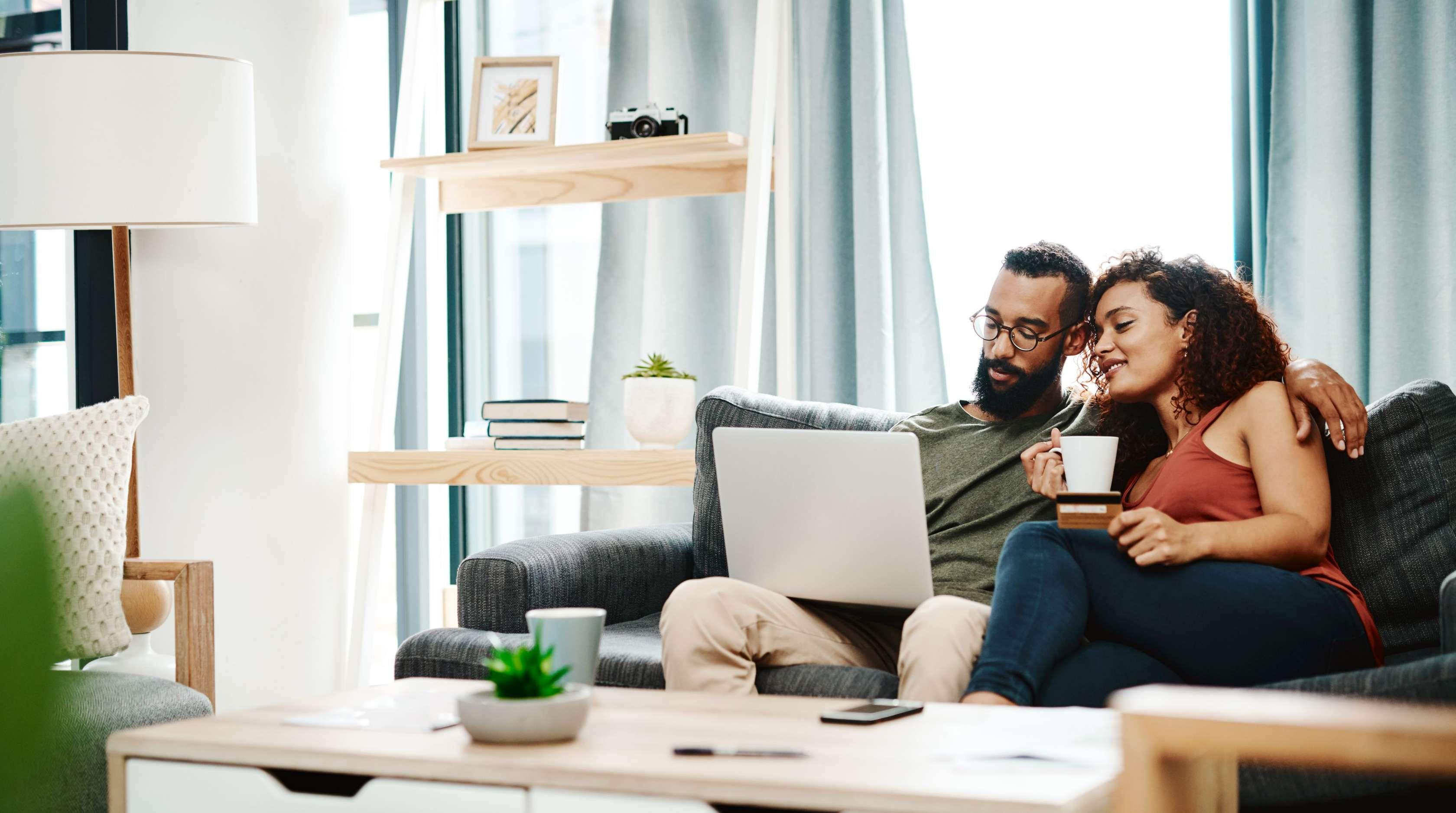 Ein Paar sitzt gemeinsam in ihrem Haus auf dem Sofa und blickt in einen Laptop.
