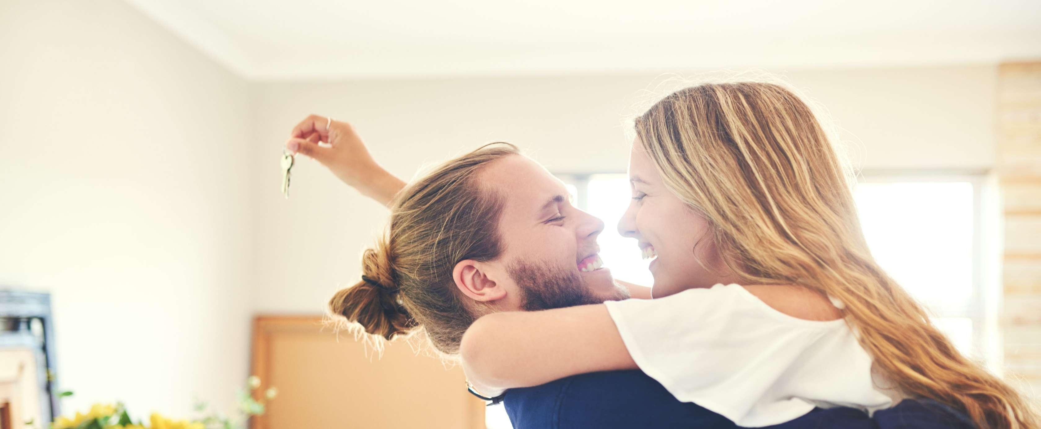 Ein junges Paar hält sich im Arm und lächelt sich fröhlich an. Im Hintergrund sieht man ihr neues Haus, sie hält den neuen Hausschlüssel in der Hand.