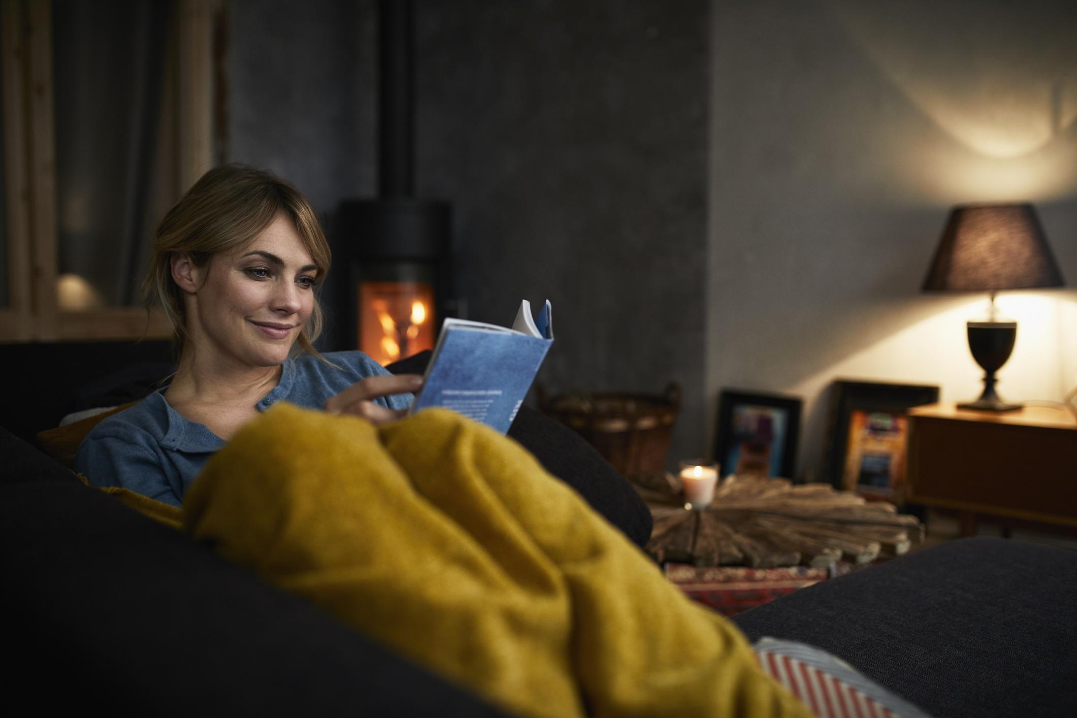 Frau sitzt in eine Decke gehüllt in Wohnzimmer und liest ein Buch