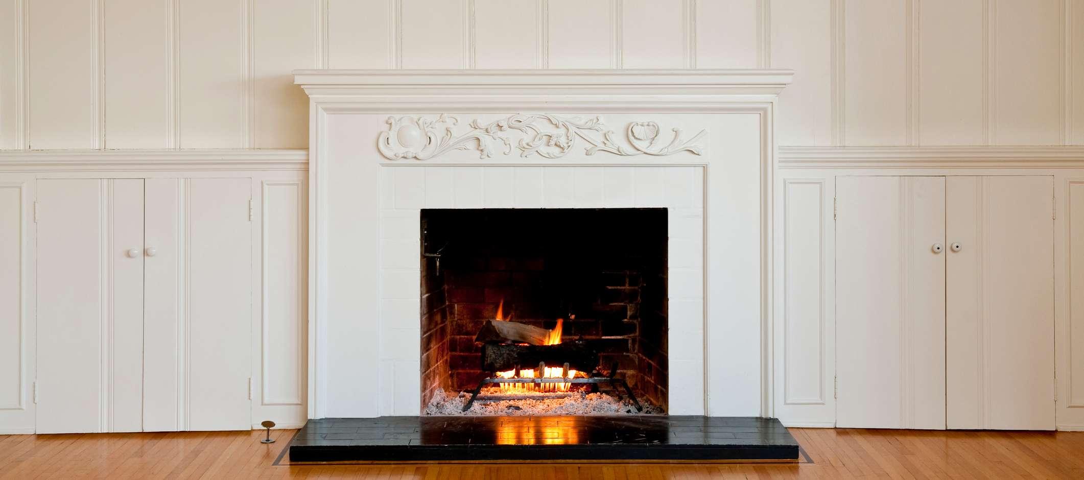 Feuer brennt in offenem Kamin in weiß getäfeltem Wohnzimmer