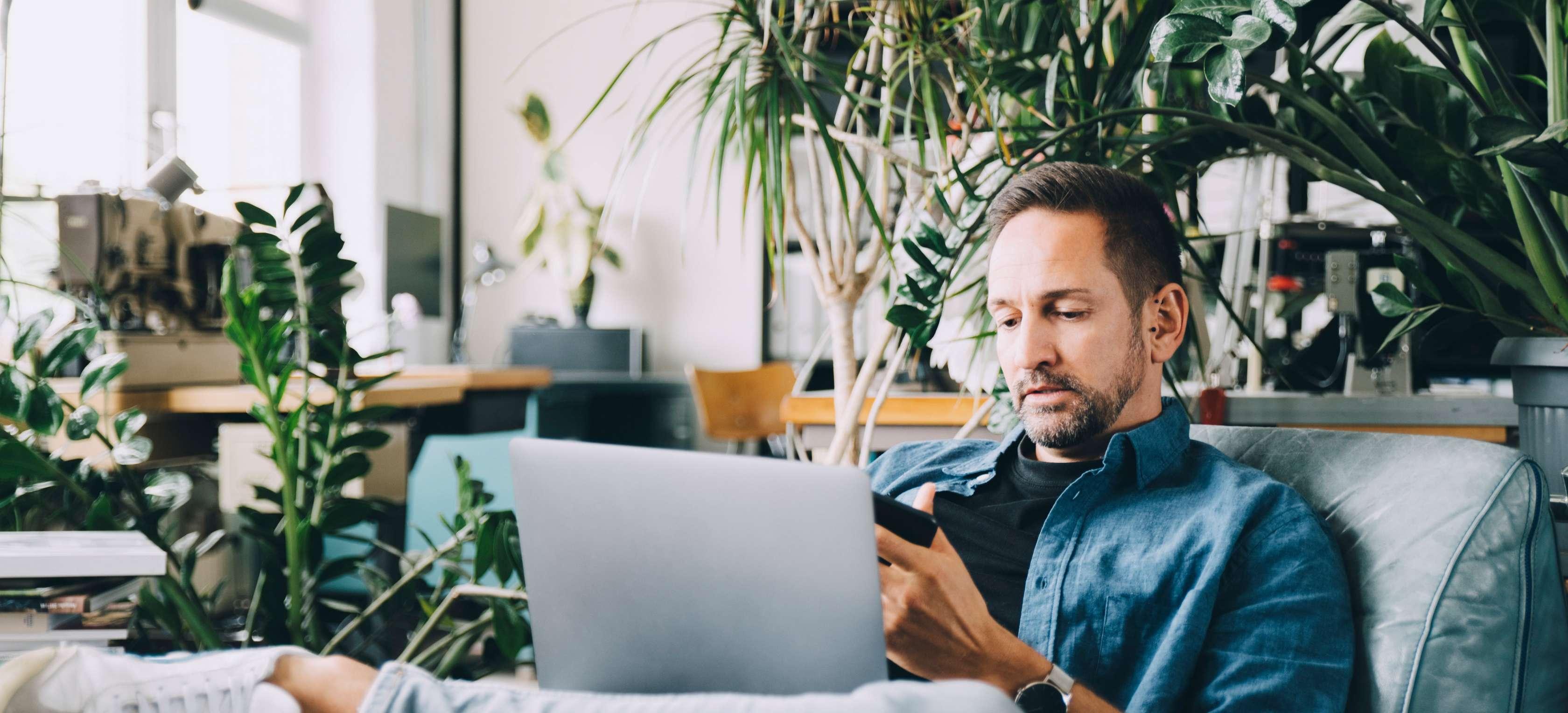 Mann schaut in einen Laptop und ein Smartphone, während er auf der Couch sitzt