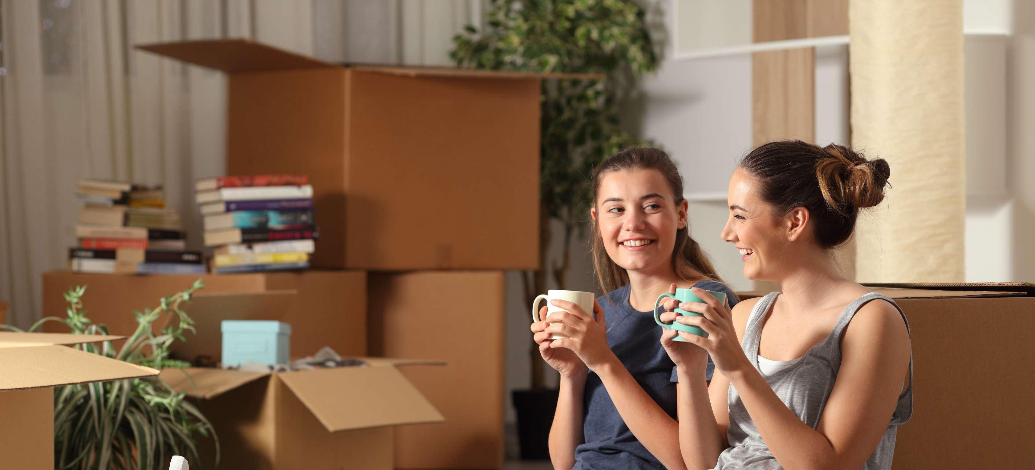 Zwei Mädchen sitzen vor Umzugskartons und trinken Kaffee