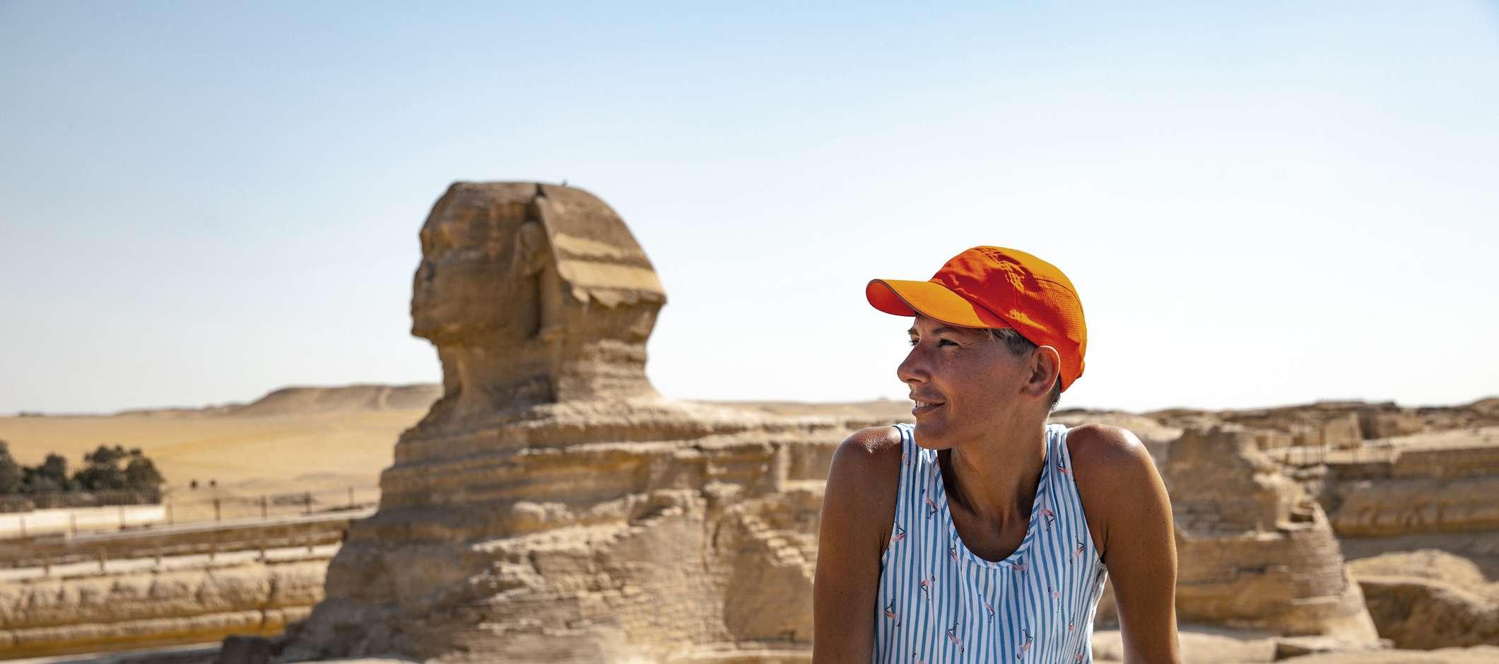 Eine Frau sitzt in der ägyptischen Wüste vor einer Sphinx