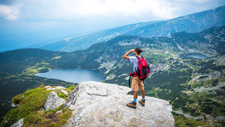 Mann steht auf Felsen und Blickt auf  bulgarischen Bergesee