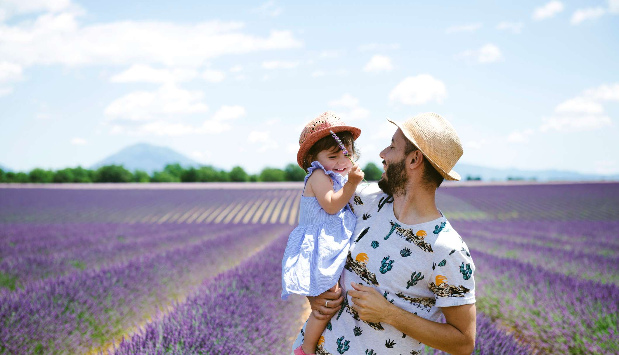 Vater und kleine Tochter stehen in einem Lavendelfeld