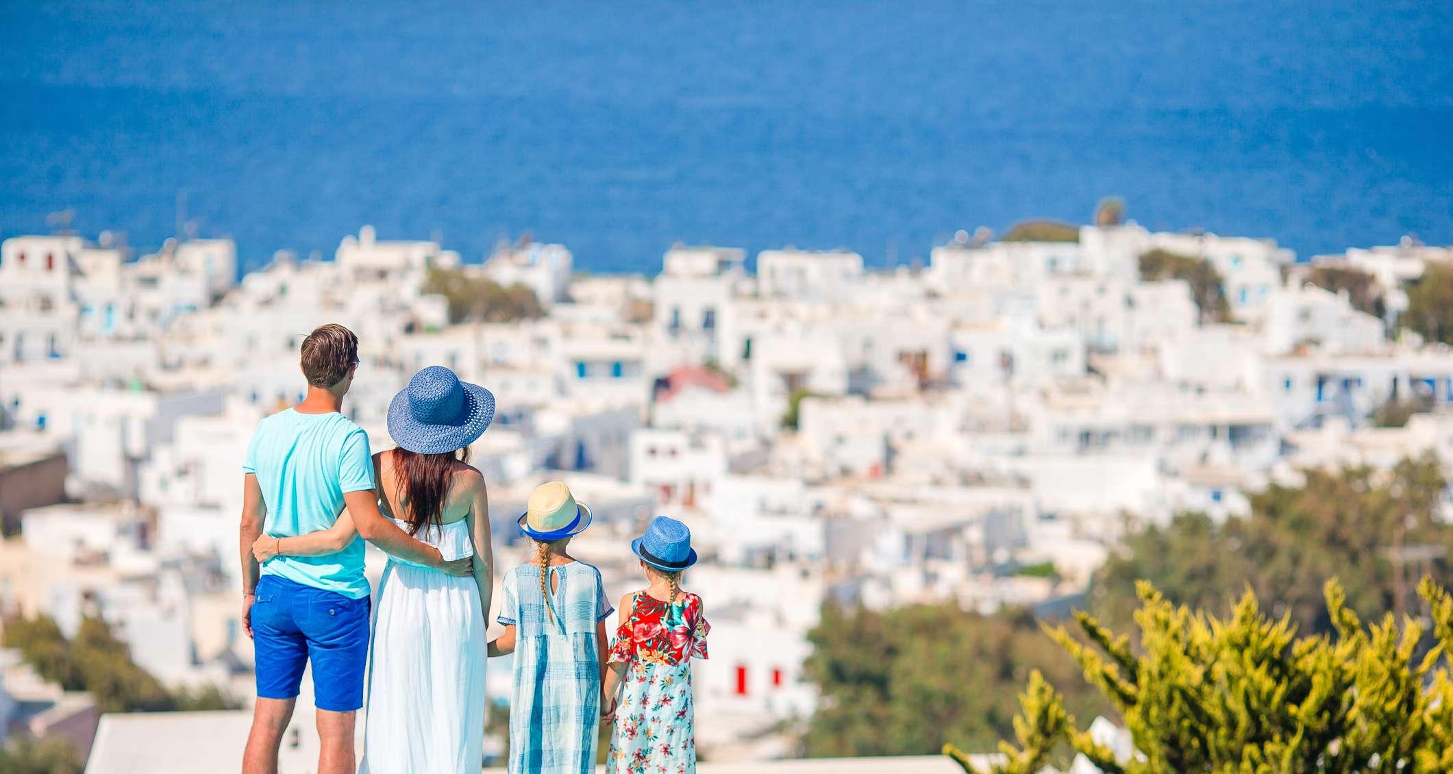 Familie blickt auf griechische Stadt am Meer