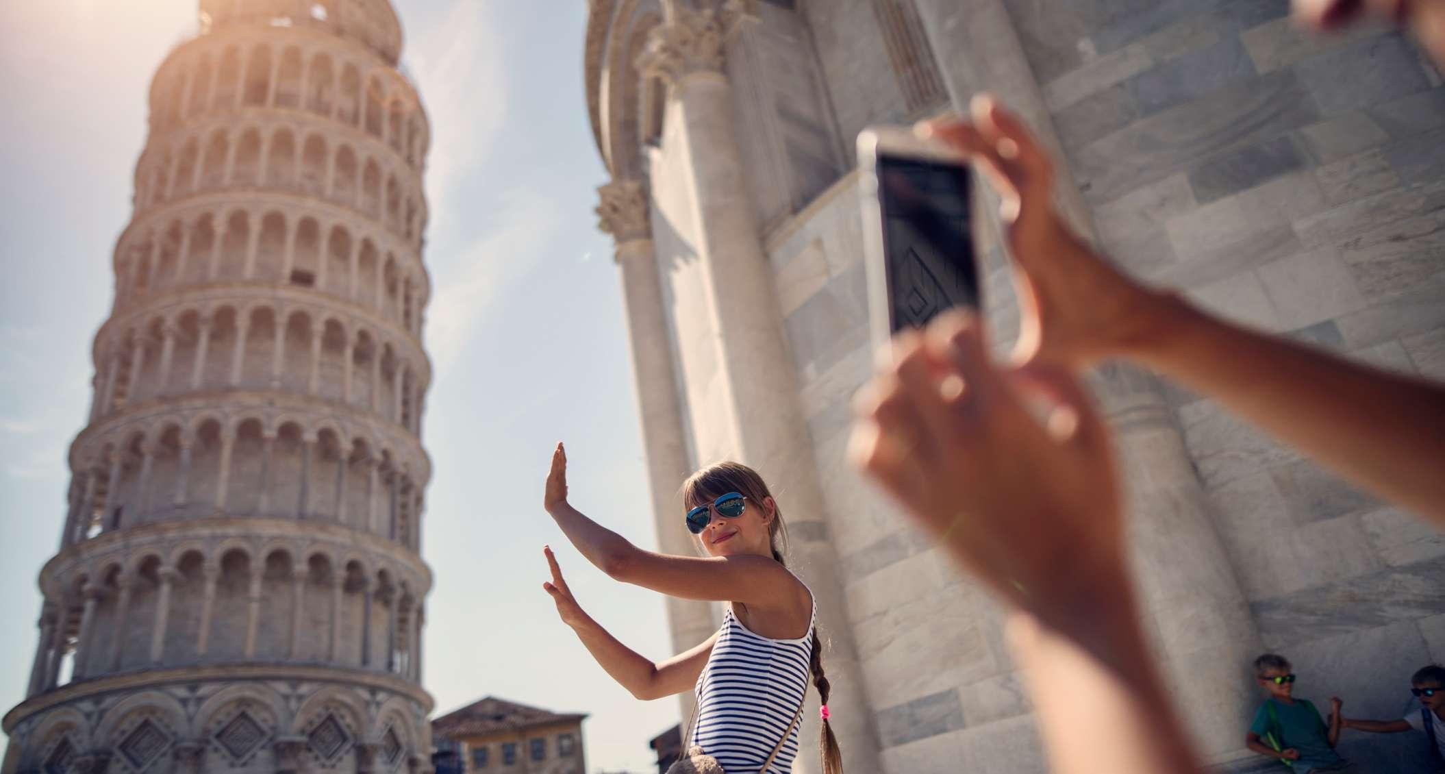 Junge Frau wird vor dem schiefen Turm fotografiert
