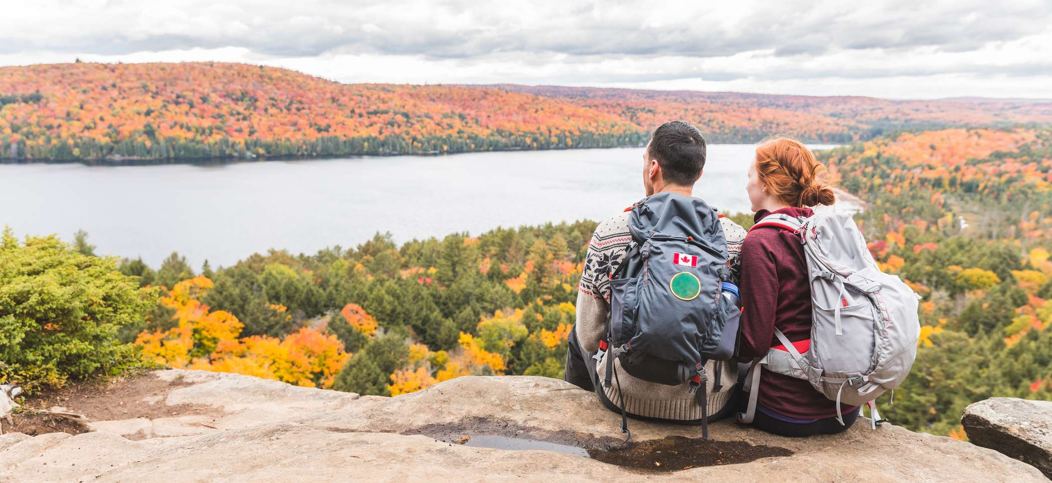 Junges Paar mit Rucksäcken sitzt auf einem Berg und sieht auf einen See