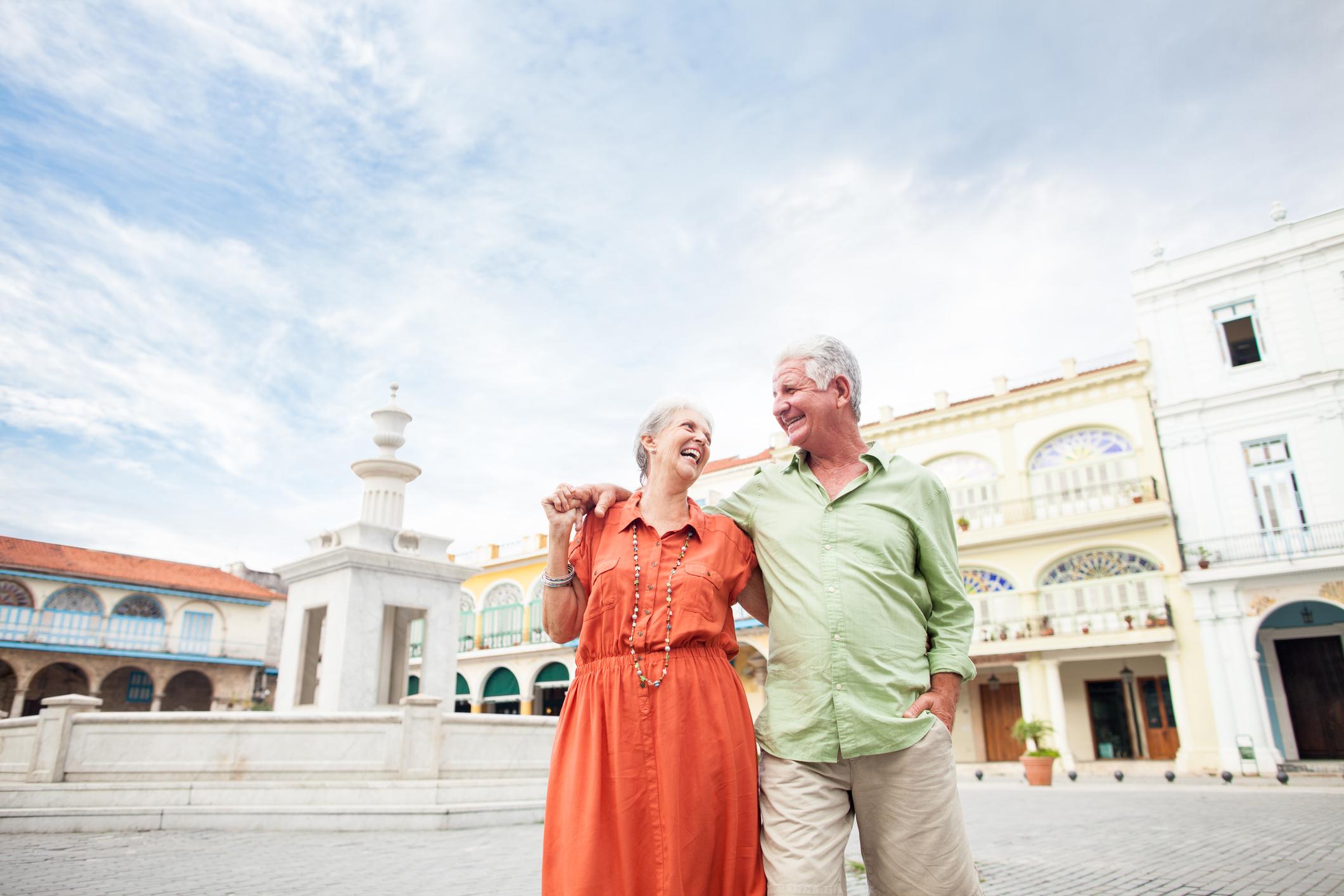 Ein älteres Ehepaar steht Arm in Arm vor typisch kubanischen Gebäuden