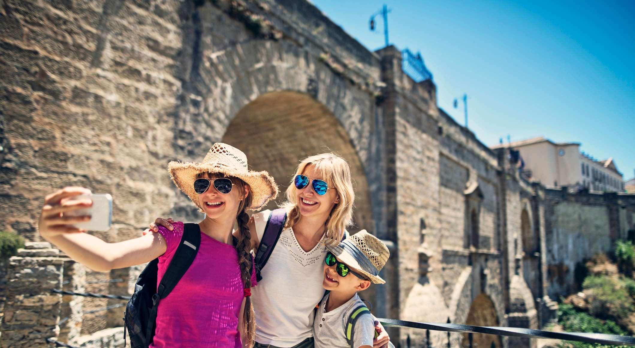 Mutter, Tochter und Sohn machen ein Foto vor einer historischen spanischen Stadtmauer