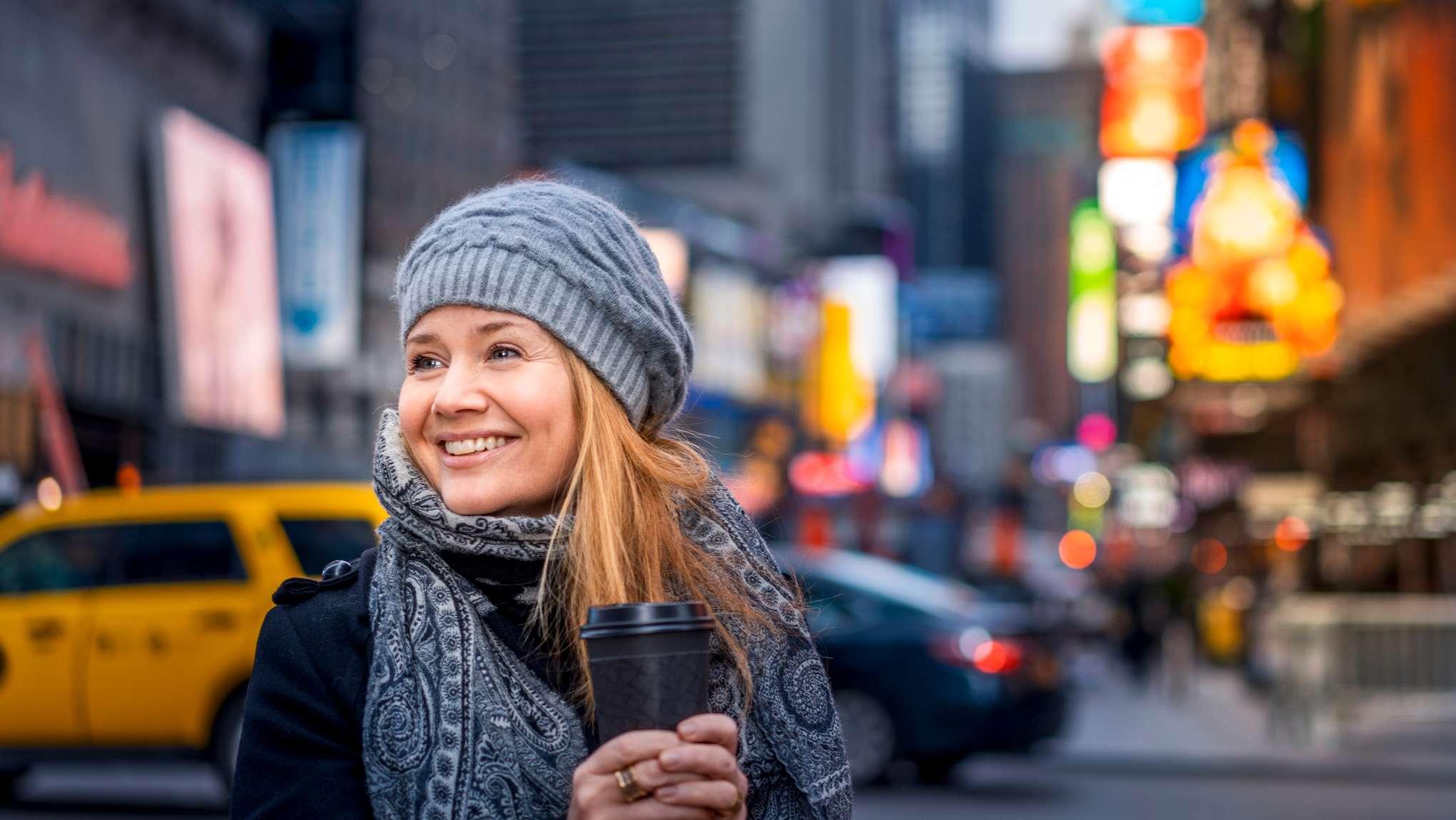 Blonde Frau mit grauer Mütze steht am Times Square