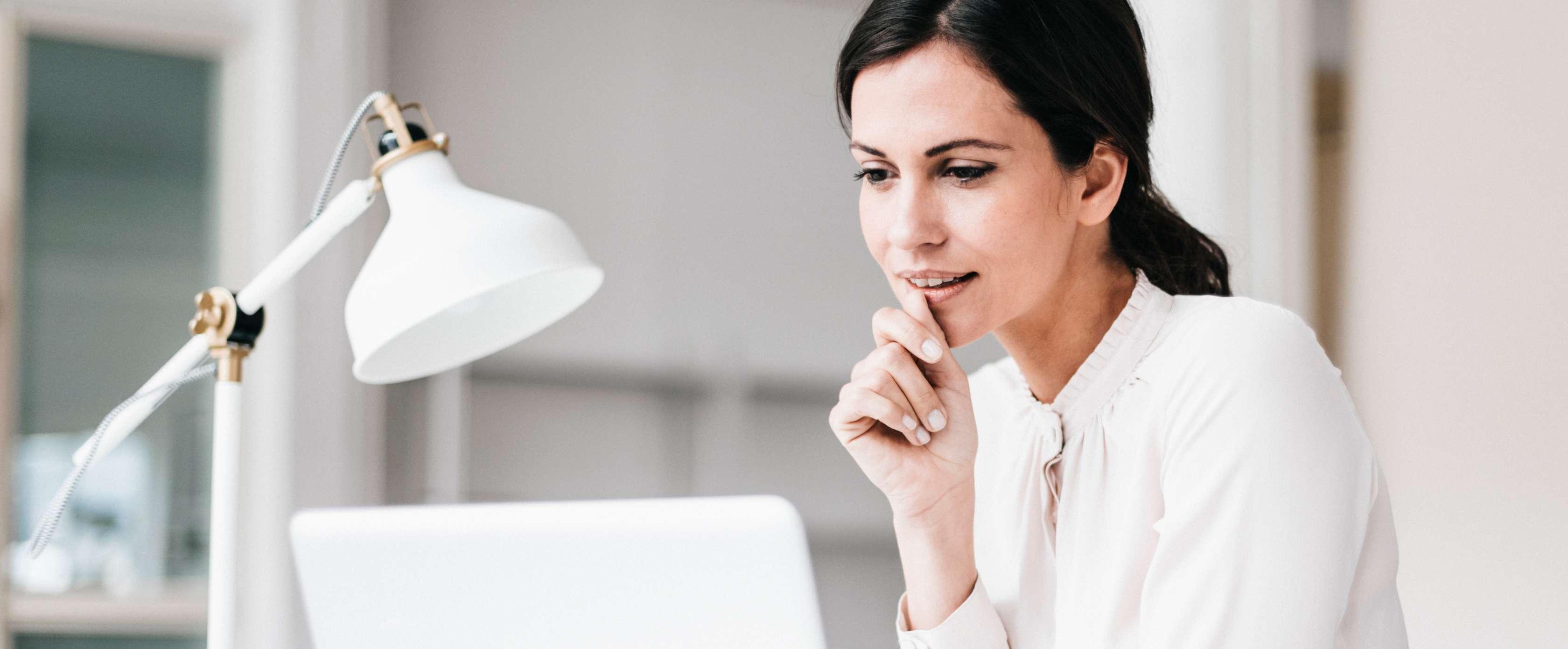 Eine lächelnde Frau arbeiten an ihrem Laptop