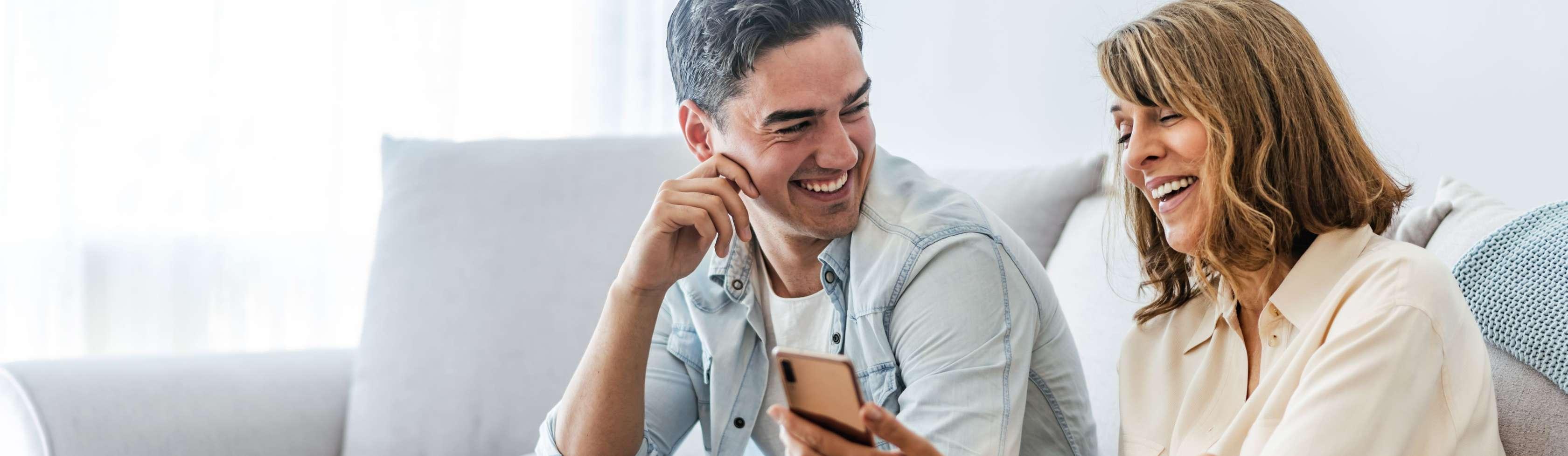 Ein Pärchen sitzt gemeinsam auf ihrem Sofa im Wohnzimmer. Während der Mann seine Partnerin anlächelt, blickt die Frau lächeld in ein Smartphone.