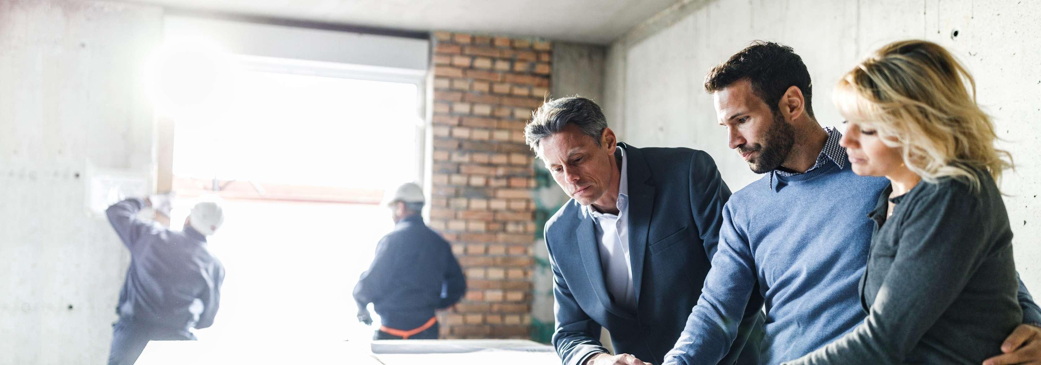 Ein Paar bespricht etwas mit dem Bauleiter auf der Baustelle, im Hintergrund stehen zwei Bauarbeiter an einem Fenster