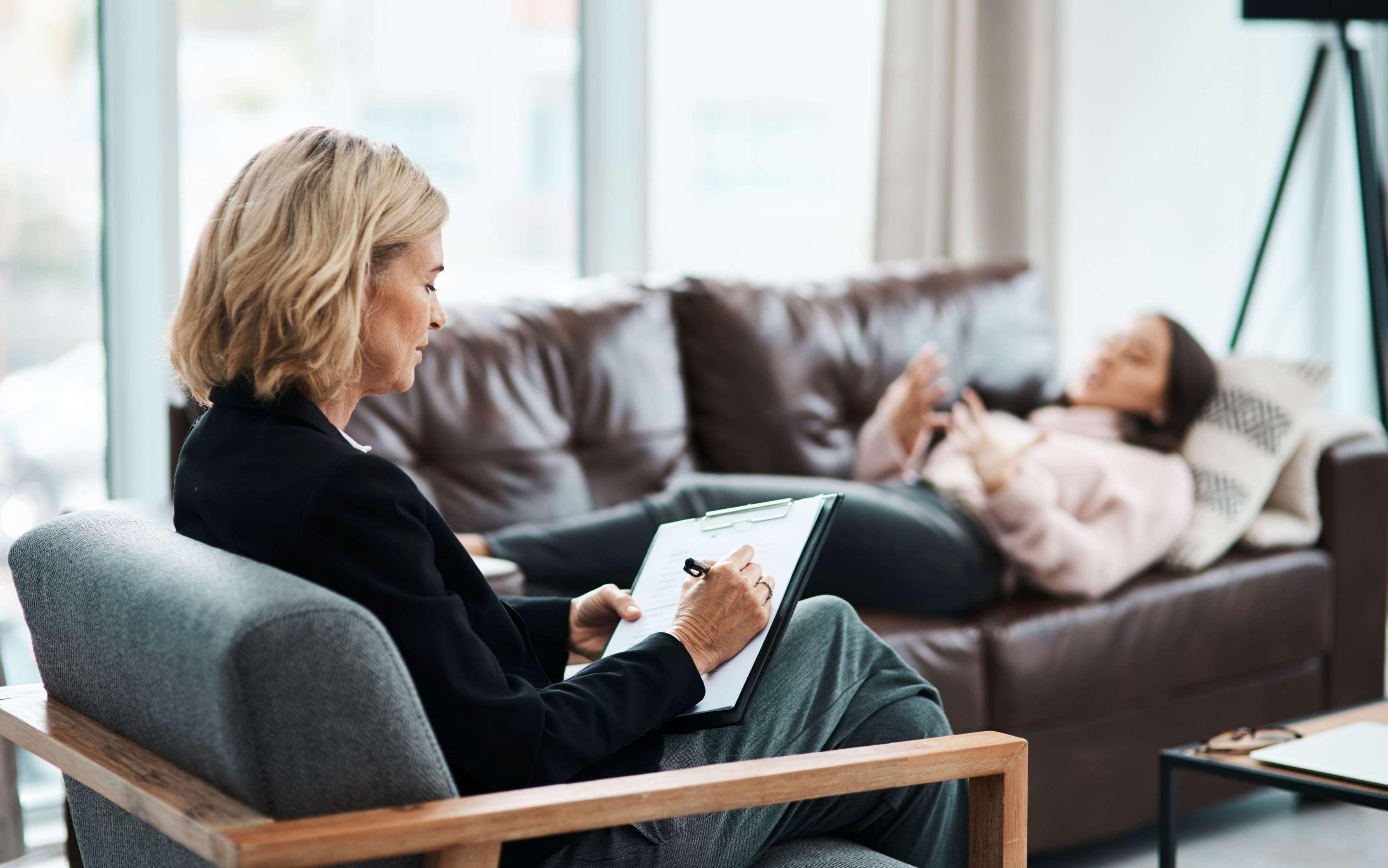 Eine Psychotherapeutin sitzt in einem Stuhl, eine Patienten liegt auf einem Sofa