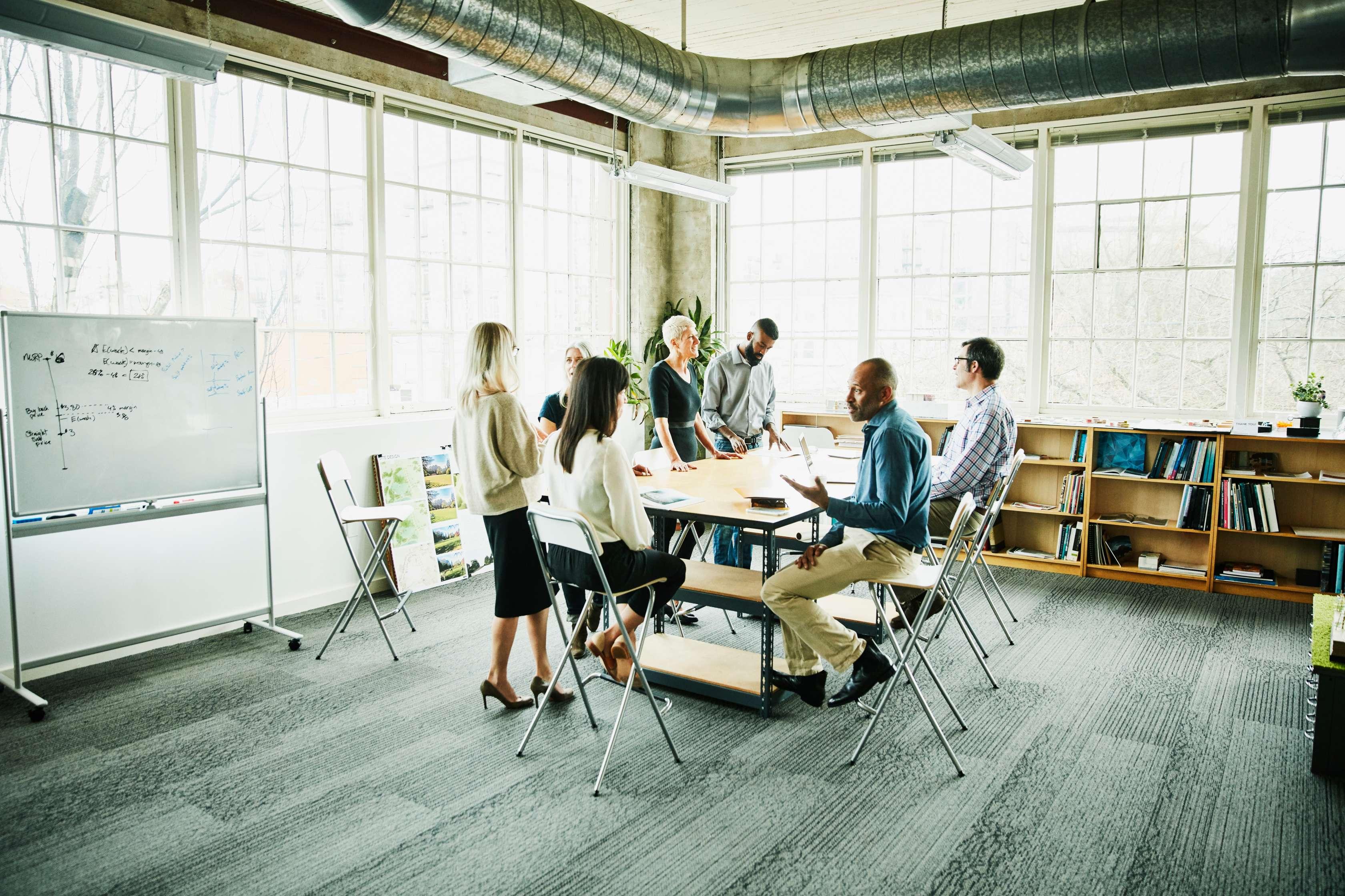 Eine Gruppe Arbeitskollegen sitzen gemeinsam in einem Besprechungsraum und diskutieren.