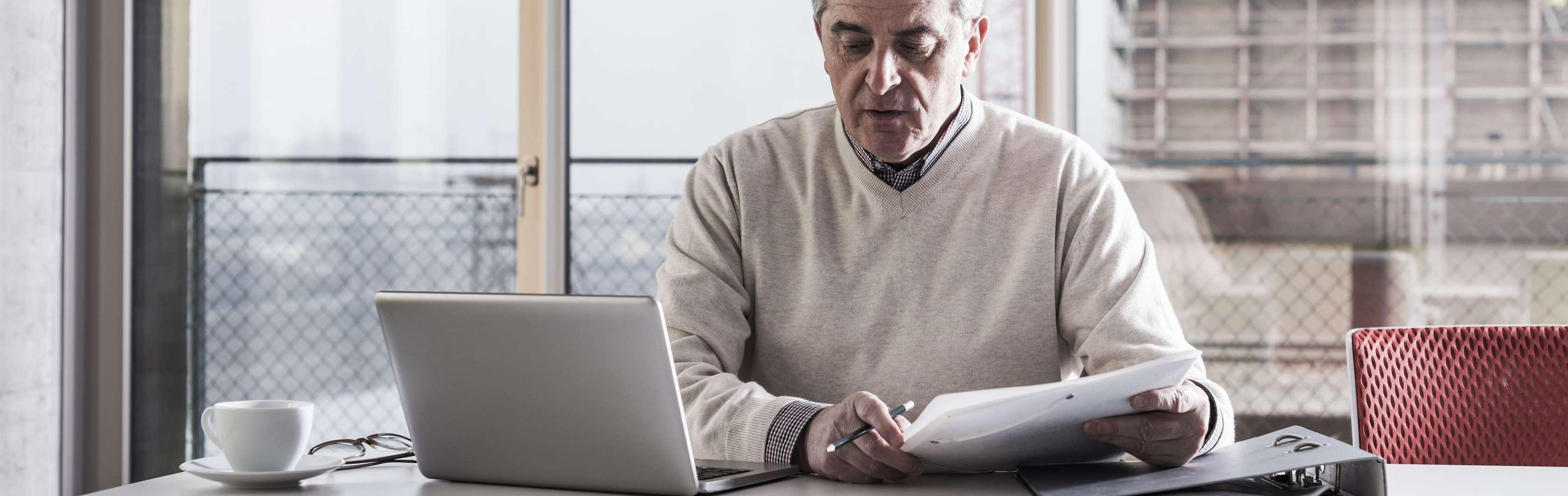 Älterer Mann sitzt mit Laptop an Besprechungstisch
